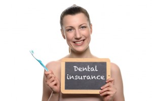 Woman smiling with dental insurance sign needs to visit her dentist in midlothian